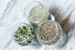 Three types of herbs. In jars on wooden background stock photos