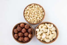 Three types of nuts in a round wooden form. (hazelnuts, pine nuts, cashews) on a white background Royalty Free Stock Photo