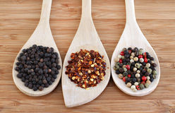 Three types of pepper on wooden spoons Stock Photos
