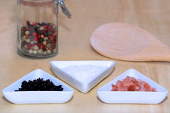 Three types of salt. With colored peppercorns and cooking spoon Royalty Free Stock Photos