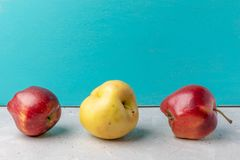 Three ugly apples on concrete table on turquoise background. Three ugly apples are lying on concrete table on turquoise painted wooden  background. Waste zero stock image