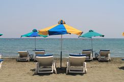 Three umbrellas and six sun beds on a beach. Six empty sun beds and three multi colored canvas umbrellas on a sandy beach in front of the Mediterranean sea and royalty free stock photography
