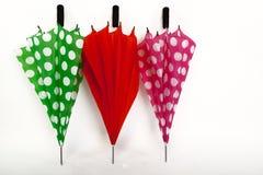 Three Umbrellas on a White Isolated Background. Three Colourful Folded Umbrellas on a White Isolated Background Stock Photos