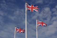 Three Union Jacks flying proudly against blue sky. And white clouds Royalty Free Stock Photos