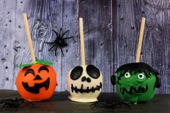Three Halloween candy apples against a spooky wood background royalty free stock image