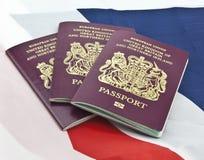 Three United Kingdom passports. On folded Union Jack Flag Stock Photography