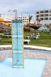 Three units shower is on sunbathing area of a hotel, green grass and sunbeds around. Three units shower is on sunbathing area of a hotel, green grass and sunbeds royalty free stock photography