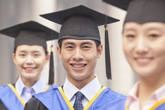 Three University Graduates Smiling in a Row Stock Image