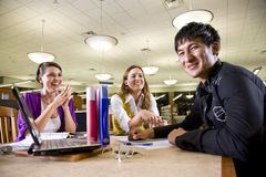 Three university students studying together. Two pretty female college students studying with handsome male student in school library Stock Images