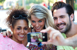 Three university students taking a selfie in the street. Stock Images