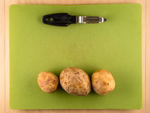 Three unpeeled potatoes on green plastic board. Several three unpeeled potatoes in a row on green plastic board with peeler, simple food preparation illustration Royalty Free Stock Images