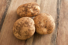 Three Unwashed Potatoes on a Wooden Table Stock Photography