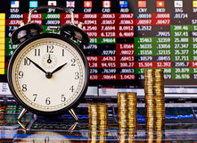 Three uptrend stacks of golden coins, clock and financial chart Royalty Free Stock Image