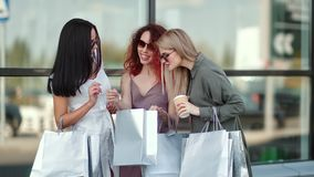 Three сurious fashion woman showing purchases looking shopping bag having positive emotion