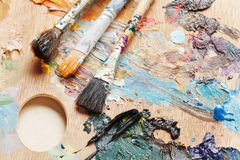 Three used paint brushes on artistic pallette Royalty Free Stock Image