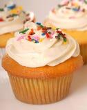 Three vanilla cupcakes with sprinkles