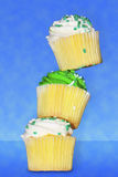 Three vanilla cupcakes tacked on top of each other. Three delicious vanilla cupcakes with green and white buttercream frosting stacked on top of each other Royalty Free Stock Photo