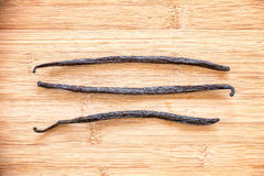 Three vanilla pods aligned on wood. En background Royalty Free Stock Photo