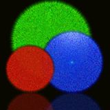 Three varicoloured fluffy balls on a black background Royalty Free Stock Images