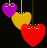 Three varicoloured fluffy hearts on a black background Stock Photography