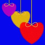 Three varicoloured fluffy hearts on a blue background Stock Image
