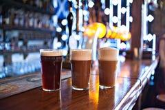 Three varieties of freshly brewed natural beer on a dark pub Stock Images