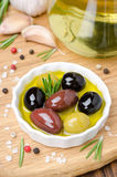 Three varieties of olives in a bowl with olive oil and spices Stock Image