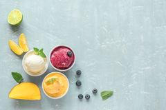 Various fruit and berries ice creams. Three various fruit and berries ice creams on blue background, copy space. Frozen yogurt or ice cream with lemon, mango royalty free stock photography