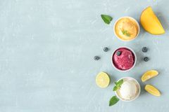 Various fruit and berries ice creams. Three various fruit and berries ice creams on blue background, copy space. Frozen yogurt or ice cream with lemon, mango Royalty Free Stock Photos