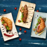 Three various tasty sandwiches with vegetables. Lettuce, mushrooms and sauce lying on flat rectangular plates on blue aged wooden surface. Delicious branch Royalty Free Stock Images