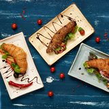 Three various tasty sandwiches with vegetables. Lettuce, mushrooms and sauce lying on flat rectangular plates on blue aged wooden surface. Delicious branch Stock Photo