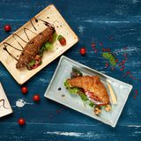 Three various tasty sandwiches with vegetables. Lettuce, mushrooms and sauce lying on flat rectangular plates on blue aged wooden surface. Delicious branch Stock Image