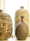 Three Vases. Three modern brown vases in front of gauzy curtains Stock Images