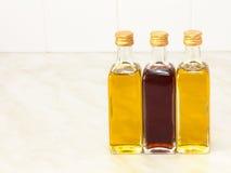 Three vegetable oil bottles on white kitchen table. Stock Image