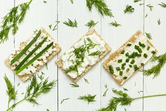 Three vegetarian breakfasts made from toast with cottage cheese and greens on a white wooden table, diet royalty free stock image