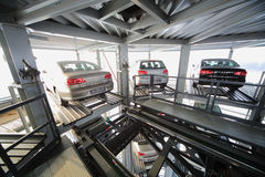 Three vehicles on the top floor of a transparent construction Stock Photo