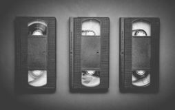 Three video cassettes on a gray background. Retro technology fro. M the 80s. Top view royalty free stock photo