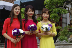 Three vietnamese young women with flowers Royalty Free Stock Images