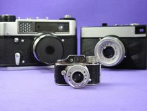 Three vintage analog photographic cameras. One of them is a miniature. stock photos