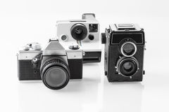 Three vintage analogue cameras. On a white background Stock Images