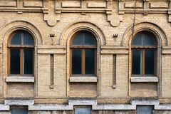 Three vintage arched windows in a wall of yellow bricks. Green - the colors of sea wave glass in a maroon dark red. Wooden frame. The concept of antique vintage Royalty Free Stock Photography
