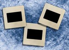 Three  vintage blank slide photo frames. Three retro blank  slide photo framework against an blue old paper, grunge background Stock Photo