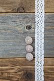 Three vintage bone buttons and lace tape. On the aged wooden surface stock photography