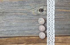 Three vintage bone buttons and lace tape. Three vintage bone buttons and lace ribbon on the aged wooden surface stock photography
