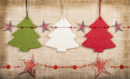 Three vintage christmas trees background with stars. Three vintage christmas trees on burlap background with red stars and vignette Stock Image