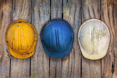 Three vintage construction helmets on a wooden wall. Three vintage construction helmets hanging on an old wooden wall Royalty Free Stock Photo
