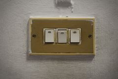 Three vintage electric light switch on the old wall stock photos