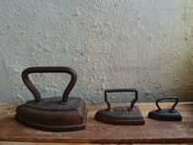 Three vintage iron on a wooden board Royalty Free Stock Photo