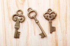 Three vintage keys on wooden background Stock Photos