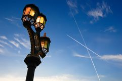 Three vintage lamps shining against a blue evening sky stock photography